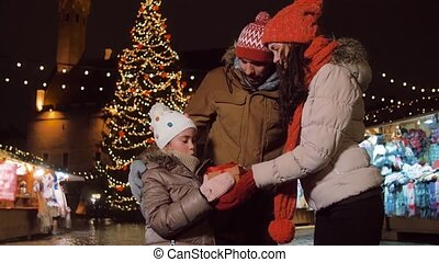 happy family with gift at christmas market in city - winter ...