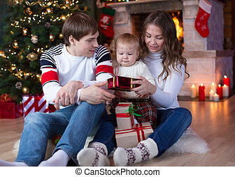 Happy family with gifts sitting at Christmas tree near fireplace