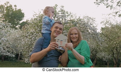 Happy family with house model as real estate concept