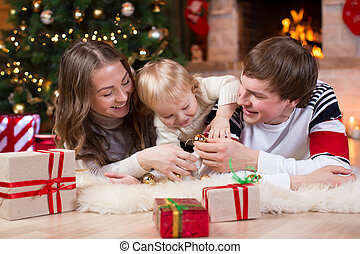 Happy family with kid son have a fun pastime near Christmas tree and fireplace in living room
