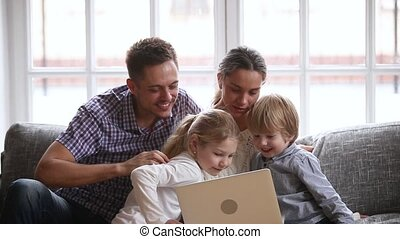 Happy family with kids having fun using laptop together