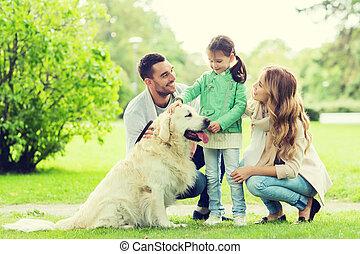happy family with labrador retriever dog in park - family,...