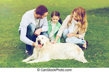 happy family with labrador retriever dog in park - family,...