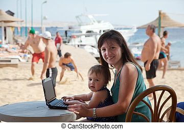 happy family with laptop at beach