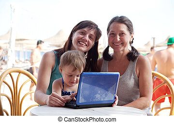 family with laptop at resort beach