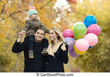 happy family with little child and air-balloons, outing in ...