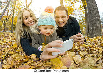 happy family with little child take Selfie on telephone, ...
