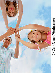 Happy family with little girl against sky, foreshortening from below, having joined hands, focus on daughter