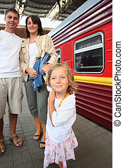 Happy family with little girl at railway station, focus on daughter