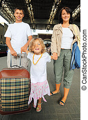 Happy family with little girl at railway station, focus on parents