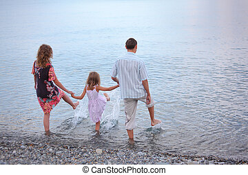 Happy family with little girl go in