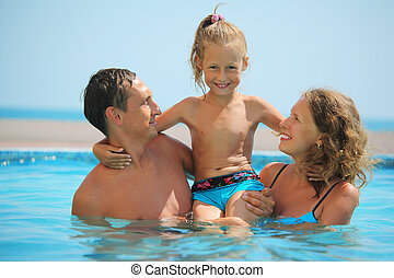 happy family with little girl have fan in pool
