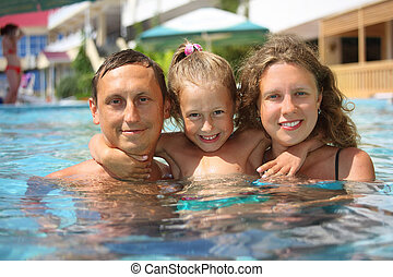 happy family with little girl in water hugging