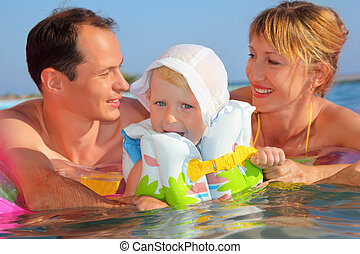 Happy family with little girl in white hat and lifejacket bathing in pool against sea, Parents looking against each other