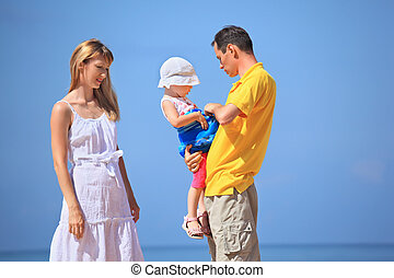 Happy family with little girl in white hat against sea