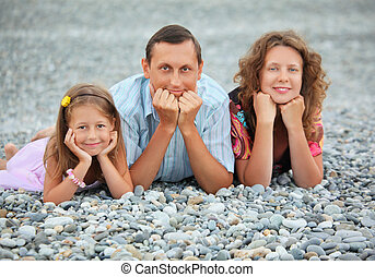 Happy family with little girl lying on stony beach, focus on father