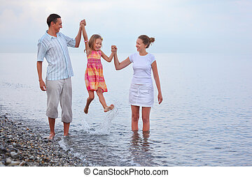 Happy family with little girl on beach in evening, parents lift girl for hands