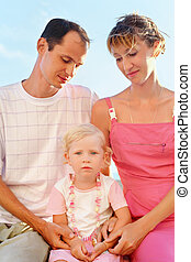 Happy family with little girl on beach, parents looking at girl
