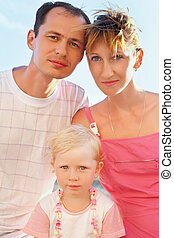 Happy family with little girl on beach, Steadfastly looking