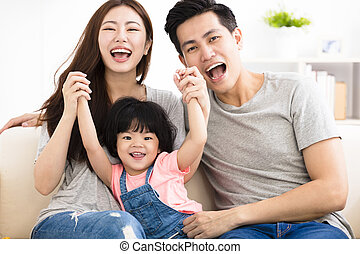 happy family with little girl  playing on the sofa