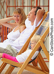 Happy family with little girl reclining on chaise lounges on veranda
