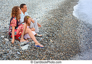 Happy family with little girl sitting on stony beach, Looking afar