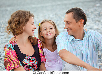 Happy family with little girl sitting on stony beach, parents looking at daughter