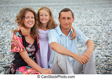 Happy family with little girl sitting on stony beach