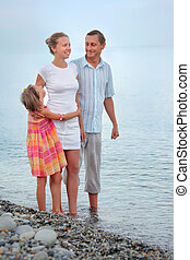Happy family with little girl standing on beach in evening, looking at mother