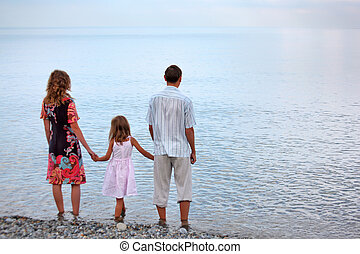 Happy family with little girl standing on beach in evening, standing back