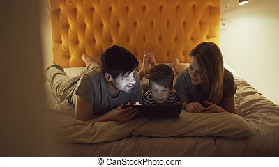 Happy family with little son a lying in bed at home and using tablet computer for watching cartoon movie before sleeping