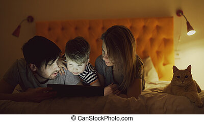 Happy family with little son and funny cat lying in bed at home and using tablet computer for watching cartoon movie before sleeping