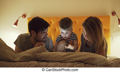 Happy family with little son learning to play tablet computer lying in bed at home in evening