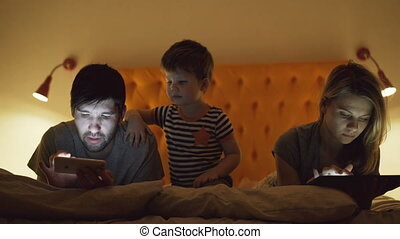 Happy family with little son lying in bed at home using tablet computer and smartphone for watching movie and cartoon in evening before sleeping