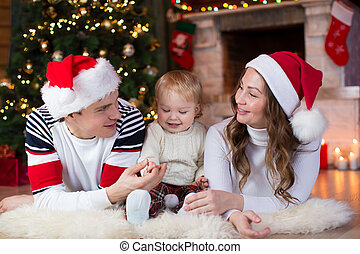 Happy family with little son lying near Christmas tree and fireplace