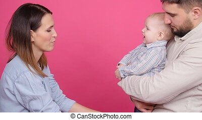 Happy family with little son over pink background