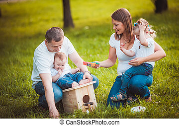 Happy family with nesting box and paints
