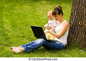 Happy family with notebook on the grass