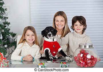 Happy Family With Pet Dog During Christmas