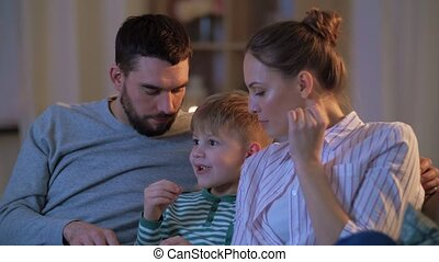 happy family with popcorn watching tv at home