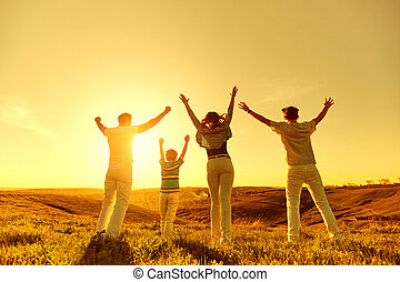 Happy family with raised hands on nature at sunset.