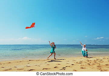Happy family with red kite on the sea beach