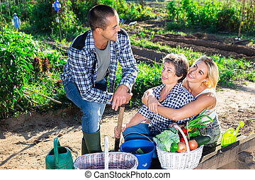Happy family with ripe vegetables harvest in garden
