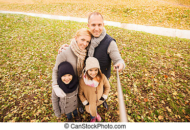 happy family with selfie stick in autumn park - family,...
