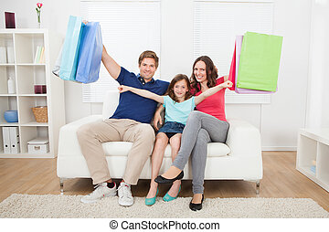Happy Family With Shopping Bags At Home