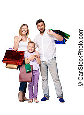 Happy family with shopping bags standing at studio