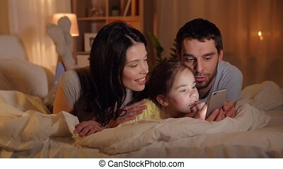 happy family with smartphone in bed at home - people and...