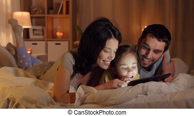 happy family with tablet pc in bed at home