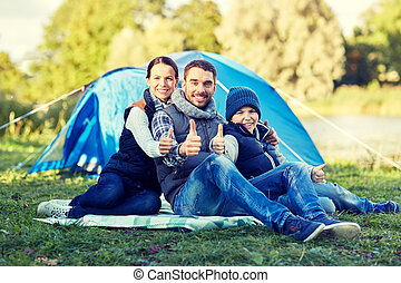 camping, tourism, hike and people concept - happy family over tent at camp site showing thumbs up gesture
