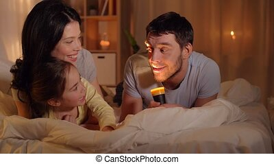 happy family with torch light in bed at home - people and...